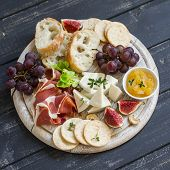 delicious appetizer to wine - ham cheese grapes crackers figs nuts jam served on a light wooden board and two glasses with white wine on wooden surface poster