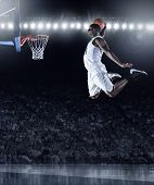Basketball Player scoring an athletic, amazing slam dunk in a professional basketball game poster