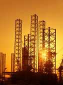 Industrial background: conceptual photo of construction facilities against bright rising sun poster