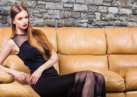 Woman In Classic Black Dress In Luxury Interior.