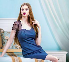 Woman In Blue Nightie In Luxury Bedroom Interior.