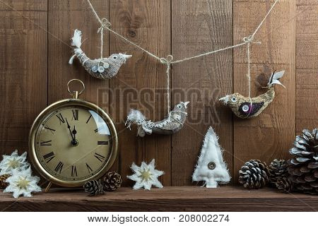 Rustic Christmas Eve scene with clock and handmade fabric decorations. Birds stars and Christmas tree. On a dark wooden background with pine cones. Time almost midnight almost Christmas day!