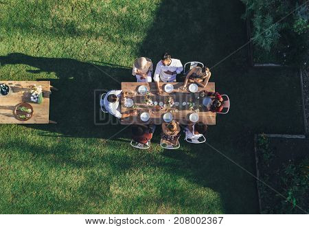 Aerial view of friends enjoying meal at outdoor party. Group of people sitting around a table in garden restaurant and having meal together.