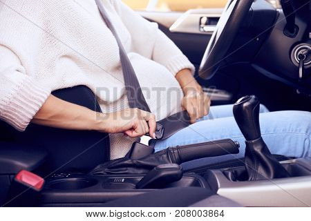 Cropped shot of hands of pregnant woman buckling seat belt in car