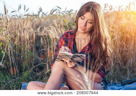 Beautiful brunette girl in a field, shirt. Concept new ideas, writing in notebook. A woman writes in a notebook. The journalist reads a diary of the note.