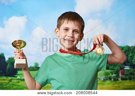 Boy Winner With Cup And Medal On Nature