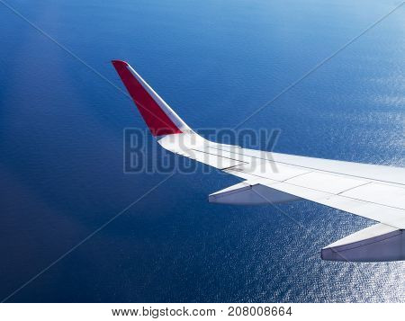 Airplane wing flight flying in sky over blue sea and reflect with sun light. Travel concept.