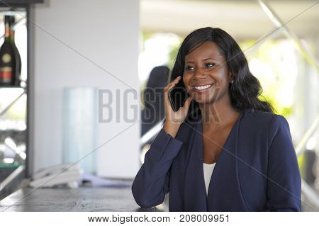 young attractive and happy black african american woman working from restaurant bar talking on mobile phone making business in entrepreneur success concept and mobility