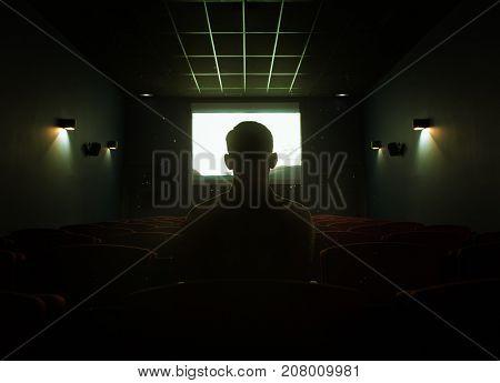 One man sitting in empty cinema hall