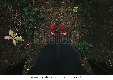 Women's legs in red boots standing in autumn forest