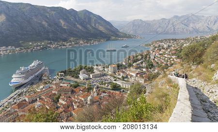 Kotor - September 26 2017: People descend from the Old Town and the big white cruise ship