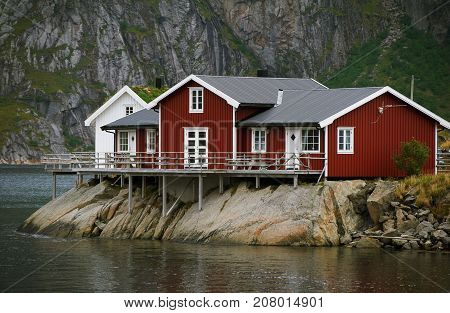 Red house on the rock near the water Lofotens Norway