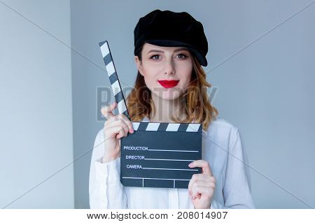 Young Redhead Woman In Hat Holding Movie Clapboard