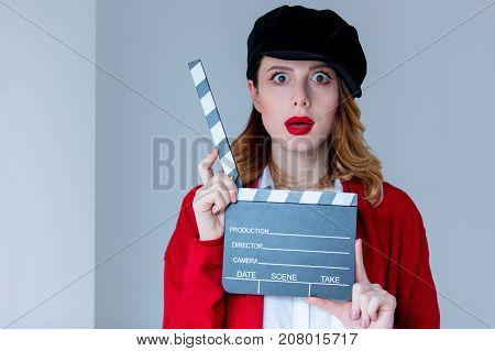 Woman In Red Cardigan And Hat With Clapboard