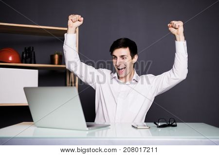 Excited Glad Young Managers Triumphing With Raised Fists In Office Over Laptop