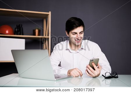 Young Happy Businessman Smiling While Reading His Smartphone. Portrait Of Smiling Business Man Readi