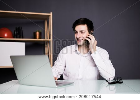 Portrait Of Businessman Talking On Mobile Phone In Office Over Laptop