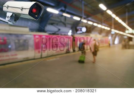 CCTV security indoor camera system operating with people waiting for sky train at train station, transportation, surveillance security and safety technology concept