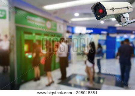 CCTV security indoor camera system operating blurred image of people queuing to withdraw money from ATM (Automated Teller Machine), finance, surveillance security and safety technology concept