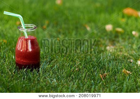 Healthy red detox drink on summer grass with free space. Fresh beet smoothie jar outdoors. Diet or healthy lifestyle, well being and weight loss concept