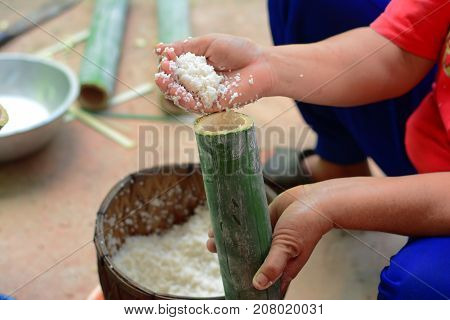 Thai Traditional Food,cooking Rice In Bamboo Joints,a Woman Puts Grain Rice With Coconut Milk In Bam