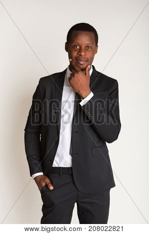 Portrait of successful african american businessman standing in suit. Vertical, isolated white background