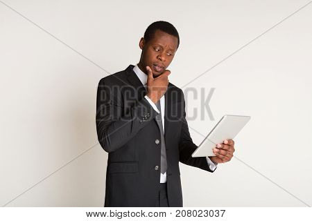 Thoughtful successful businessman in stylish suit holding tablet. Lifestyle portrait. Copy space