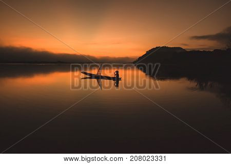 Silhouette of Fisherman catching fish in the river.
