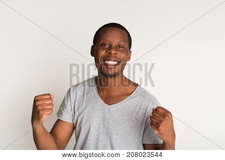 Close up portrait of happy african american male , hands are clenched into fists, white background. Human emotions, facial expressions