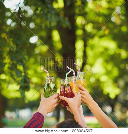 Group of people do cheers with detox juice cocktails on green nature background witn free space. Diet on the go, well being and weight loss, superfoods, health, vegetarian food concept