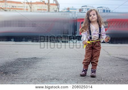 Little girl on railway station with the blured train on background