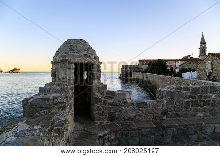 BUDVA, MONTENEGRO - SEPTEMBER 14, 2013: It is the medieval fortress wall that surrounds the old town in the evening.