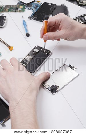 Repairman disassembling smartphone with screwdriver. Technician fixing broken phone, electronics repair service, repairer pov, copy space for text