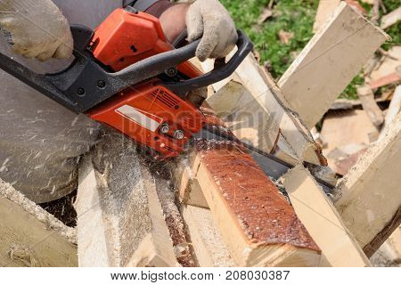 man saws wood with orange chainsaw in village
