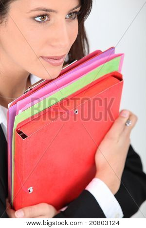 young woman dressed in suit holding file folders