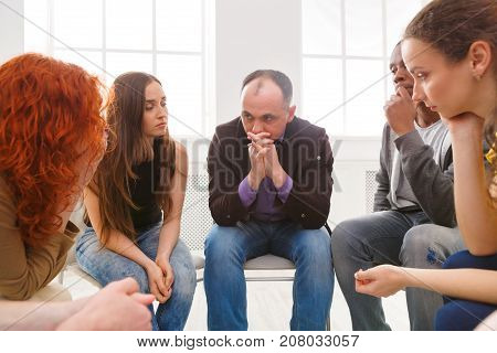 Meeting of support group. Depressed man sitting at rehab group therapy. Psychotherapy, depression, life issues concept