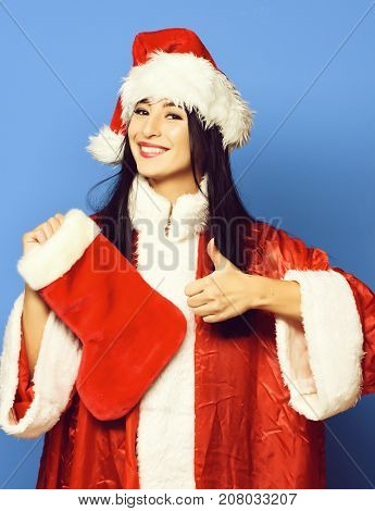 pretty cute sexy santa girl or smiling brunette woman in red sweater and new year hat holds decorative christmas or xmas stocking or boot and showing cool on blue studio background