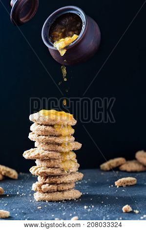 Levitating Clay Pot With Orange Jam, Over A Stack Of Cookies On Dark Rustic Background. Creative Sna