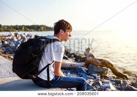 Displeased Young Man with Backpack at the Seaside