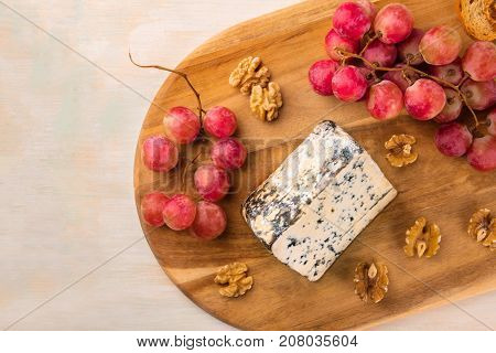 An overhead photo of a piece of Gorgonzola with vibrant grapes, slices of bread, and nuts, on a light background with a place for text
