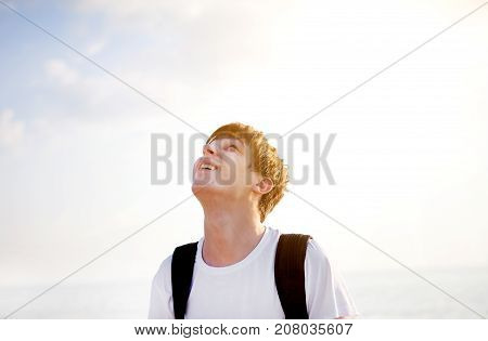 Young Man looking Up on the Sky Background