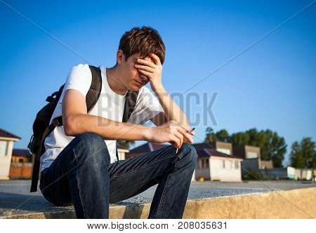 Sad Young Man with Cigarette sit on the Street
