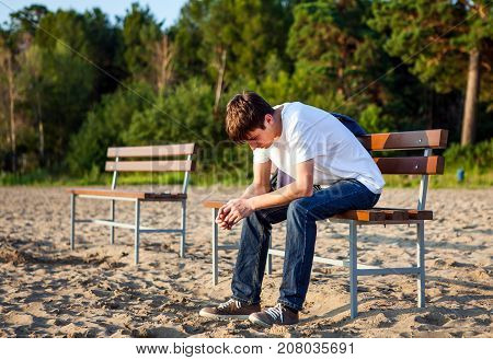 Sad Young Man sit on the Bench outdoor