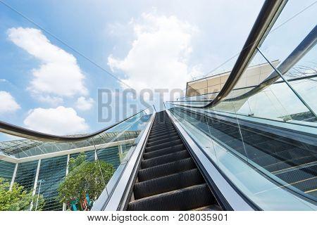 outdoors escalator near modern buildings against blue cloud sky