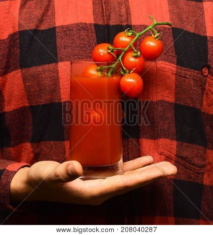 Male Hand Holds Tomato Juice On Red Plaid Shirt Background