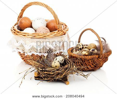 basket with eggs and quail eggs on a white background