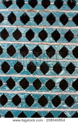 Patterned wall in blue ceramics with holes