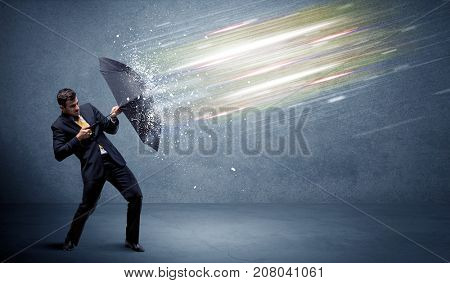 Business man defending light beams with umbrella concept on background