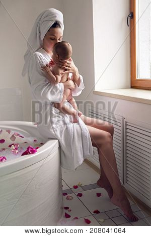 mom in a robe sitting on a round bathtub and holding a naked baby in her arms