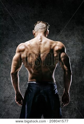 Back view. Naked torso of muscular man on dark background. Strength and motivation